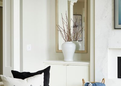 A corner of a white couch with built-in table against the wall, a large mirror, and a plant in a vase.