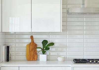 a corner of a kitchen with white countertops. Recipe books, a cutting board, and a plant sit atop.
