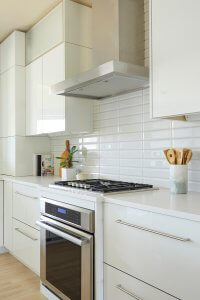 A white backsplash with stainless steel oven and range.