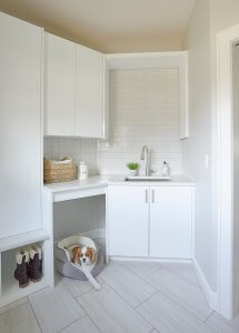 A dog lays in a dog bed in a new white mudroom.