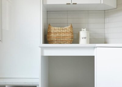 A modern white mudroom with space for a dog bed beneath the counters.