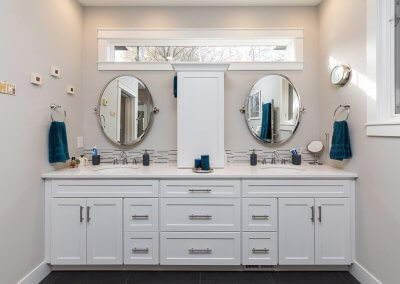 A large bathroom counterspace with a privacy window above, two mirrors, and two sinks.