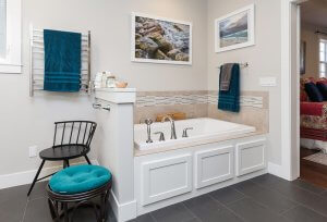 A whirlpool bathtub sectioned off in a private corner of a bathroom with blue towels and stool to accent the space.