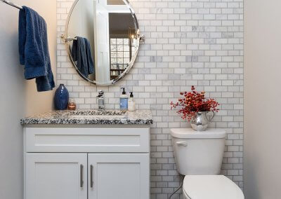 A remodeled half-bathroom with white/gray backsplash on one wall, marbled gray countertops and white cabinets.