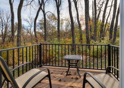 A small outdoor patio with two lawn chairs and a table overlooks a wooded fall scene.