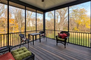 A screened-in three season porch overlooks beautiful trees.