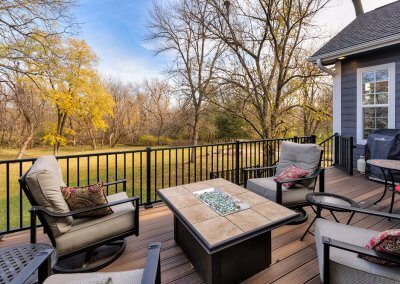 A back patio with four chairs and a fire pit in the center. A view of the backyard beyond the patio.