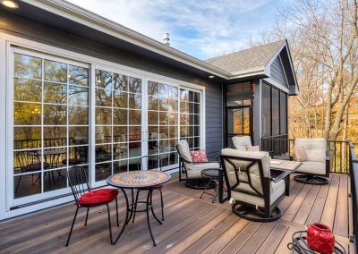 Back patio with sliding double doors and cushioned chairs.