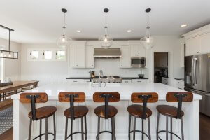 An all-white kitchen with wooden industrial-style bar stools.