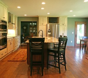 A newly remodeled kitchen with antique style. Black barstools surround a new kitchen island.