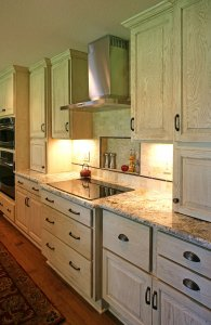 A newly renovated kitchen with antique-style cabinets and an electric stovetop.