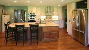A newly renovated kitchen with distressed antique-style cabinetry and a large island with marbled countertops.