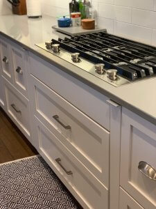 Secret, narrow spice cabinets are concealed on both sides of a stovetop.