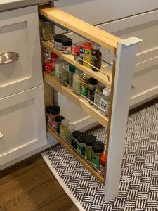 A built-in spice rack pulls out in a secret cabinet beneath a stovetop.