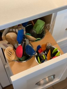A white drawer pulls out beneath a kitchen counter to reveal built-in crocks to store kitchen utensils.