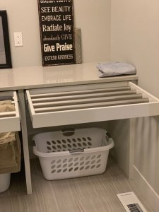 A bathroom countertop with drawers pulled out to reveal secret drying racks for hang-drying clothes.
