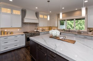 White kitchen with extended island, quartz countertops and pendant lighting.