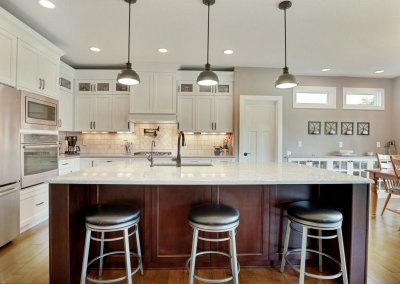 Kitchen with white cabinetry and tile back splash, counter space seating and built in buffet/display.
