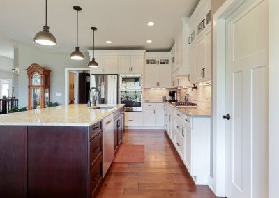 White kitchen with hardwood flooring, pendant lighting and pantry.