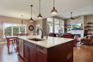Kitchen island with view into great room featuring stone fireplace, floating shelves and pendant lighting.