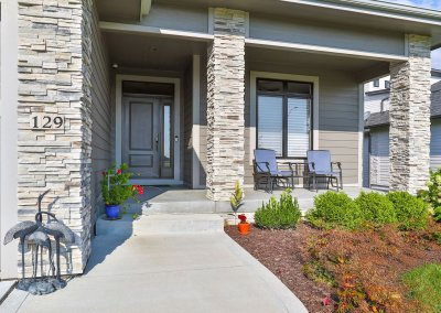 Front porch and door with landscaping and stone columns.