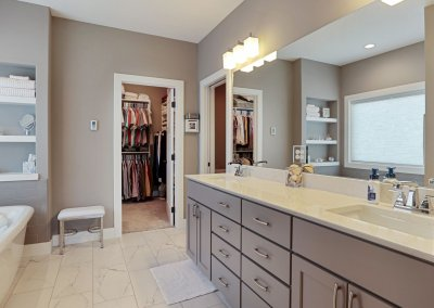 Master bathroom with dual sinks, built in shelving over bathtub, tile floor and walk in closet.