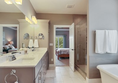 Master bathroom with dual vanity, soaking tub, walk in shower and oversize mirror.
