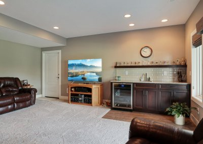 Lower level great room with wet bar, featuring tile backsplash, wine fridge and custom cabinetry.