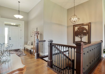 Entry and stair railing, light fixtures and hardwood flooring.