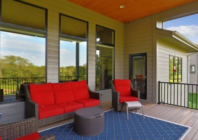 Covered patio with red deck furniture.