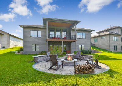 Rear exterior photo showing fire pit, circular patio, covered deck and adjacent homes.