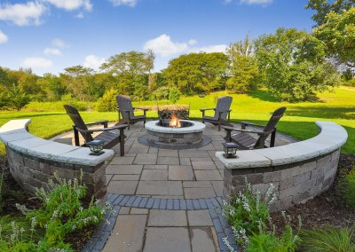 Circular shaped fire pit with Adirondack chairs, sitting wall and lighting.