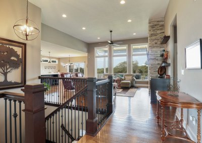 Great room view from the entry featuring floor to ceiling windows, stone fireplace and stairwell.