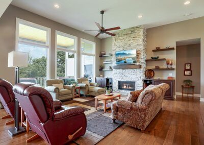 Great room with large windows, stone fireplace and floating shelves.