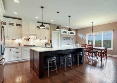 Kitchen with island, pendant lighting, hardwood floors, white tile backsplash, pot filler and glass front cupboards.