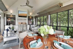 Screened in patio with outdoor kitchen, heaters, dining table, fire table, shiplap ceiling and outdoor furniture.