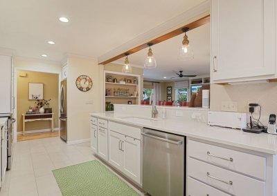 Small white remodeled kitchen with pendant lighting.