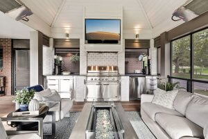 Outdoor kitchen with custom built ins, fire table, outdoor furniture and shiplap ceiling.