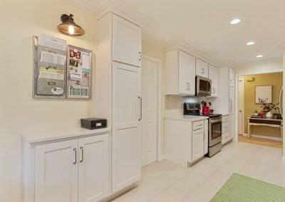 White kitchen with tile floor, bulletin board.