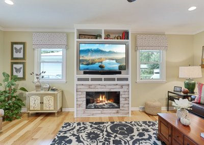 Remodeled living room with built in surrounding fireplace and television.