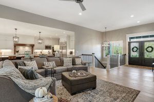 Beautifully appointed great room and kitchen with open entry, staircase and cozy gray furniture.