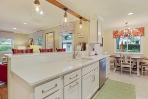 Eat in kitchen with counter and white cabinetry.