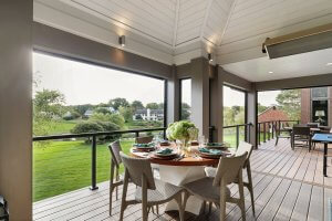 Covered deck with dining table, open air windows, drop down screens and view to backyard.