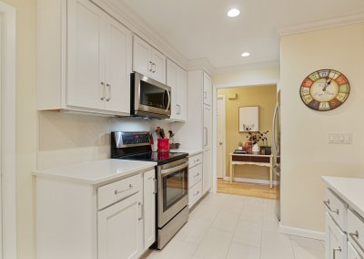 White remodeled kitchen with tile floor.