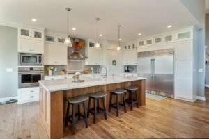 Kitchen with island, extended refrigerator, pendant lighting and tile backsplash.