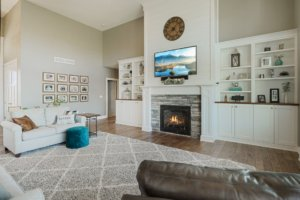Living room fireplace, white built in cabinetry and hardwood flooring.