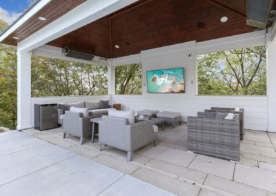 Outdoor entertainment space with covered roof, heaters, and furniture.
