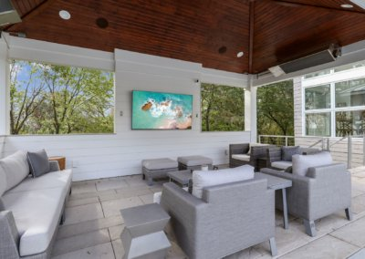 Covered patio with treated ceiling, heaters, television and outdoor furniture.