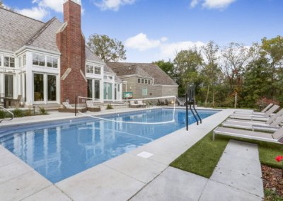 Backyard pool with lounge chairs, volleyball net and basketball hoop.