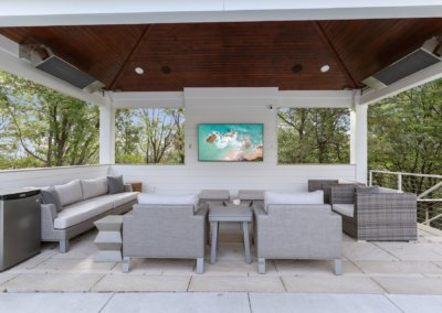 Outdoor tv area next to pool with heaters and seating.